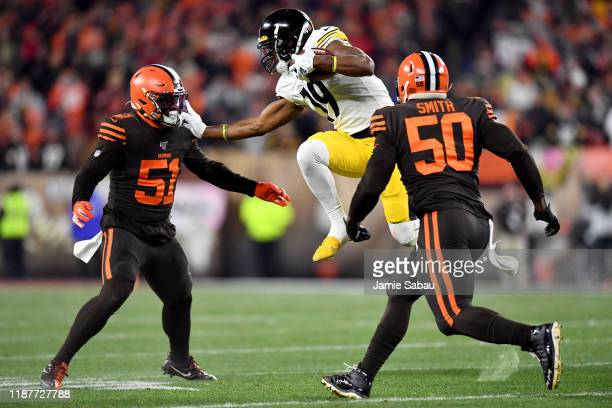Wide receiver JuJu SmithSchuster of the Pittsburgh Steelers carries the ball against the defnse of Mack Wilson and defensive end Chris Smith of the...