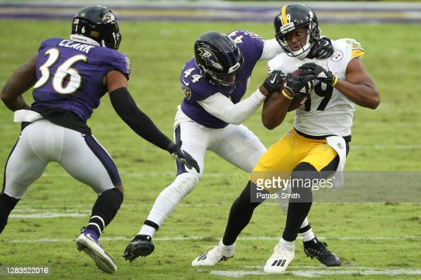 Wide receiver JuJu Smith-Schuster of the Pittsburgh Steelers is tackled by cornerback Marlon Humphrey of the Baltimore Ravens at M&T Bank Stadium on...