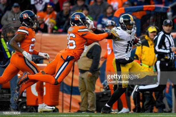 Wide receiver JuJu SmithSchuster of the Pittsburgh Steelers runs after a catch and avoids a tackle attempt by strong safety Darian Stewart of the...