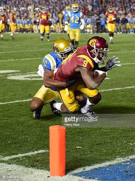 Wide receiver JuJu SmithSchuster of the USC Trojans makes a catch for a 20 yard gain as he is tackled by defensive back Fabian Moreau of the UCLA...