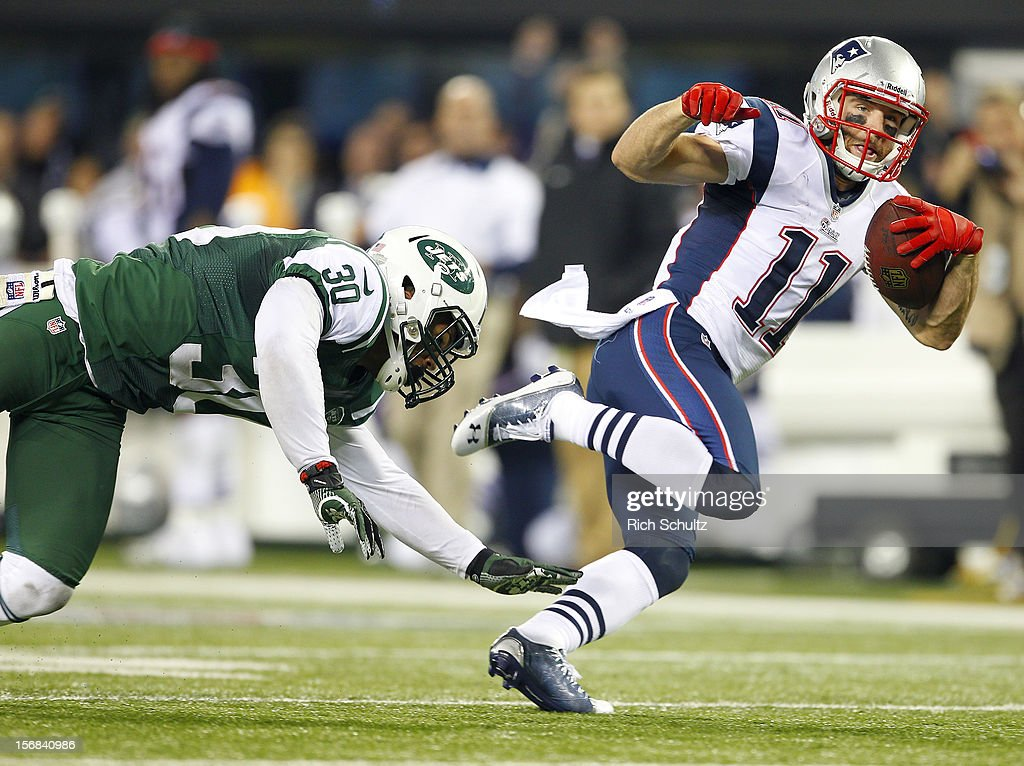 Wide receiver Julian Edelman #11 of the New England Patriots eludes LaRon Landry #30 of the New York Jets after making a catch and scores a touchdown during the second quarter of a game at MetLife Stadium on November 22, 2012 in East Rutherford, New Jersey.