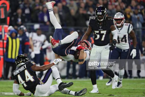 Wide receiver Julian Edelman of the New England Patriots is upended by cornerback Marlon Humphrey and linebacker Patrick Onwuasor of the Baltimore...