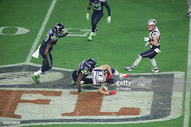 Wide receiver Julian Edelman of the New England Patriots keeps his knee off the ground on the NFL logo crest to extend a long gain against the...