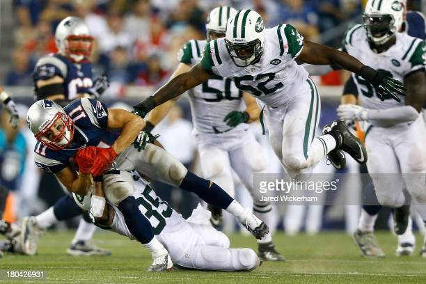 Wide receiver Julian Edelman of the New England Patriots makes a catch in front of inside linebacker David Harris of the New York Jets in the second...