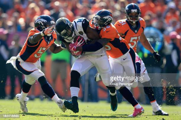 Wide receiver Justin Blackmon of the Jacksonville Jaguars makes a first down reception and is tackled by cornerback Kayvon Webster of the Denver...