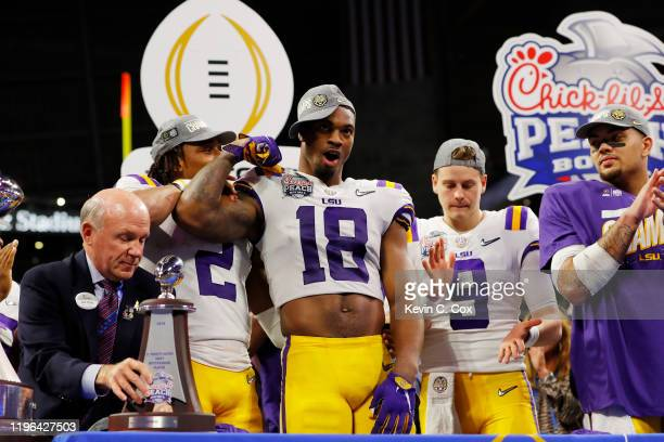 Wide receiver Justin Jefferson linebacker K'Lavon Chaisson and quarterback Joe Burrow of the LSU Tigers celebrate on the podium after winning the...