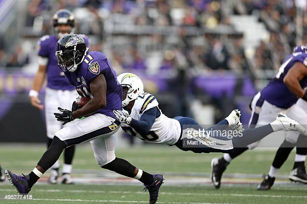 Wide receiver Kamar Aiken of the Baltimore Ravens breaks a tackle by cornerback Patrick Robinson of the San Diego Chargers in the fourth quarter of a...