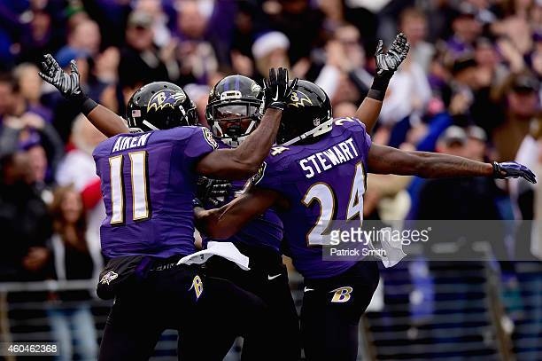 Wide receiver Kamar Aiken of the Baltimore Ravens celebrates with free safety Darian Stewart and linebacker Zach Orr after scoring a first quarter...