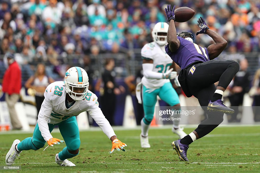 Wide receiver Kamar Aiken #11 of the Baltimore Ravens makes a catch against cornerback Bobby McCain #28 of the Miami Dolphins in the second quarter at M&T Bank Stadium on December 4, 2016 in Baltimore, Maryland.