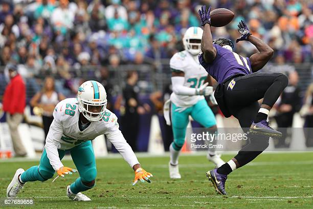 Wide receiver Kamar Aiken of the Baltimore Ravens makes a catch against cornerback Bobby McCain of the Miami Dolphins in the second quarter at MT...