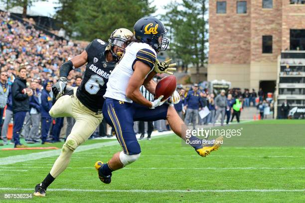 Wide receiver Kanawai Noa of the California Golden Bears comes down with a catch for a second quarter touchdown under coverage by defensive back Evan...