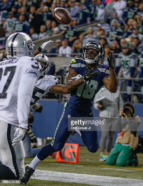 Wide receiver Kasen Williams of the Seattle Seahawks makes a touchdown catch against defensive back Chimdi Chekwa of the Oakland Raiders at...