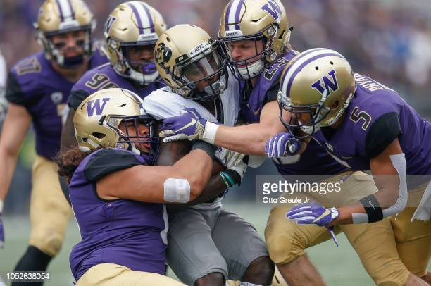 Wide receiver KD Nixon of the Colorado Buffaloes is tackled by linebacker Benning Potoa'e and linebacker Ben BurrKirven of the Washington Huskies at...