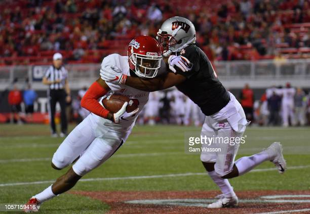 Wide receiver KeeSean Johnson of the Fresno State Bulldogs runs after catching a pass against defensive back Alex Perry of the UNLV Rebels during...