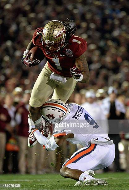 Wide receiver Kelvin Benjamin of the Florida State Seminoles is hit by defensive back Jermaine Whitehead of the Auburn Tigers in the fourth quarter...