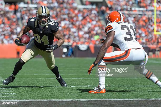 Wide receiver Kenny Stills of the New Orleans Saints caries the ball while under pressure from strong safety Donte Whitner of the Cleveland Browns...