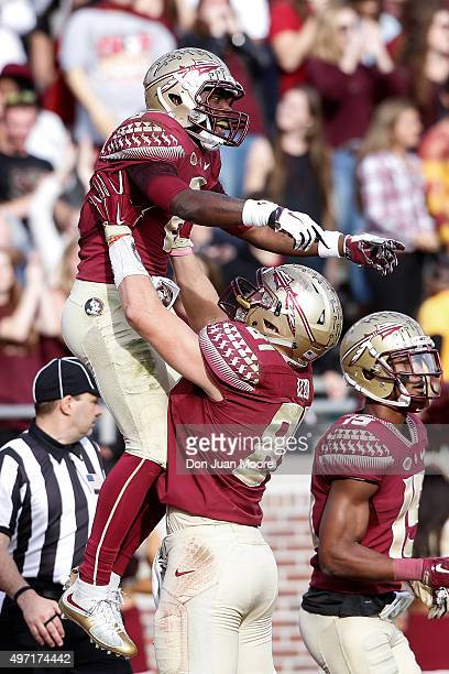 Wide Receiver Kermit Whitfield is lifted up by teammate Tight End Ryan Izzo of the Florida State Seminoles after a score during the game against the...