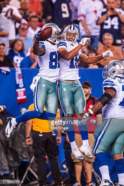 Wide receiver Kevin Ogletree of the Dallas Cowboys chest bumps Miles Austin after scoring a touchdown in the third quarter during the game against...
