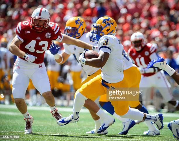 Wide receiver Khalil Thomas of the McNeese State Cowboys runs past linebacker Trevor Roach of the Nebraska Cornhuskers during their game at Memorial...