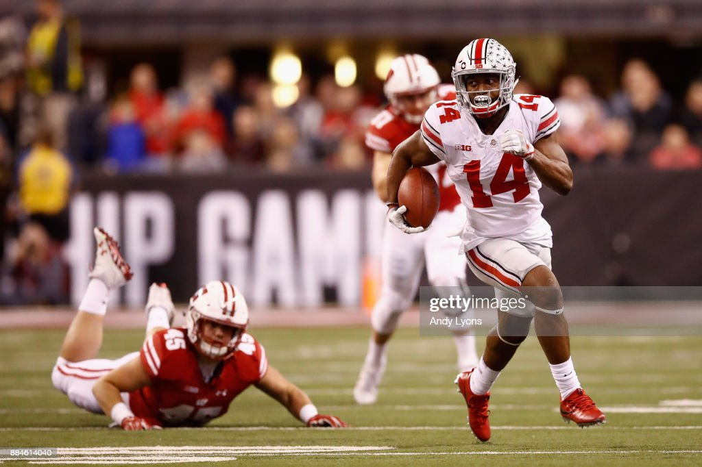 Wide receiver K.J. Hill #14 of the Ohio State Buckeyes runs the ball against fullback Alec Ingold #45 of the Wisconsin Badgers in the second half during the Big Ten Championship game at Lucas Oil Stadium on December 2, 2017 in Indianapolis, Indiana.