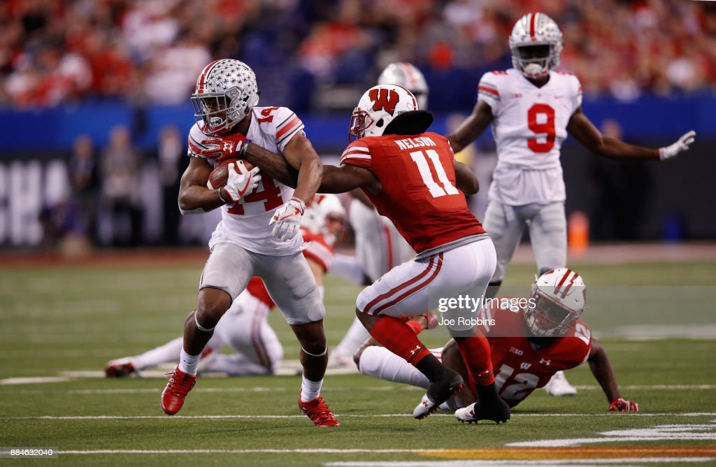 Wide receiver K.J. Hill #14 of the Ohio State Buckeyes runs the ball against cornerback Nick Nelson #11 of the Wisconsin Badgers during the Big Ten Championship game at Lucas Oil Stadium on December 2, 2017 in Indianapolis, Indiana.