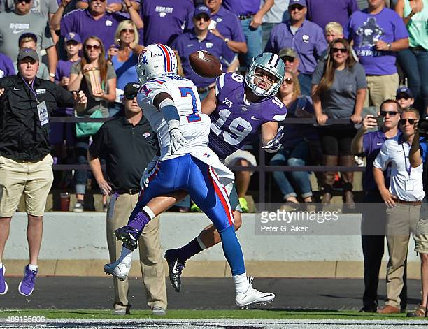 Wide receiver Kody Cook of the Kansas State Wildcats reaches around safety Xavier Woods of the Louisiana Tech Bulldogs, to catch a four yard...
