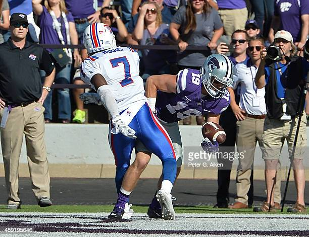 Wide receiver Kody Cook of the Kansas State Wildcats reaches around safety Xavier Woods of the Louisiana Tech Bulldogs, to catch a four-yard...