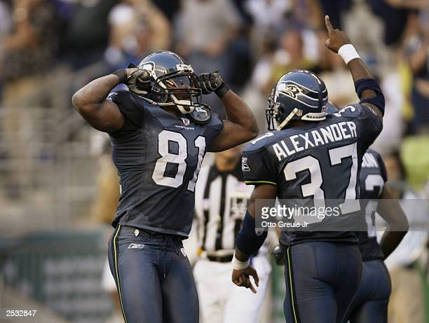 Wide Receiver Koren Robinson of the Seattle Seahawks flexes his muscles in front of teammate running back Shaun Alexander after Robinson scored the...