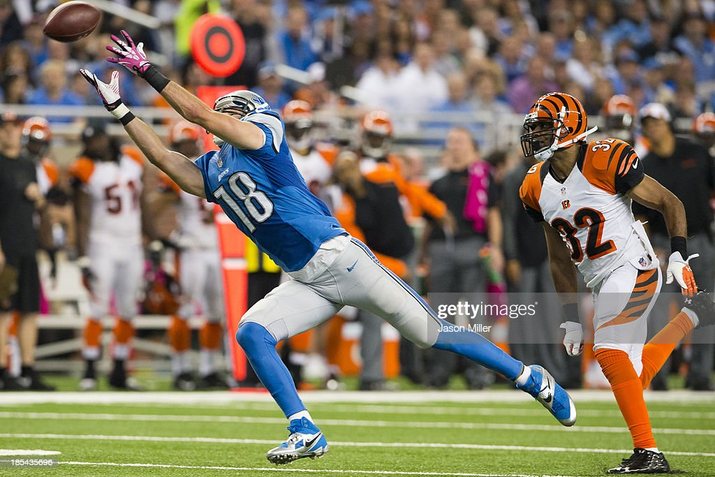 Wide receiver Kris Durham #18 of the Detroit Lions catches a pass while under pressure from defensive back Chris Crocker #32 of the Cincinnati Bengals during the first half at Ford Field on October 20, 2013 in Detroit, Michigan.