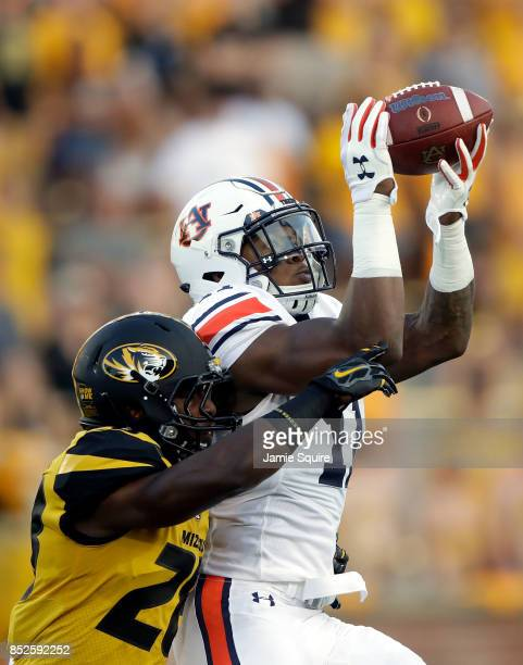 Wide receiver Kyle Davis of the Auburn Tigers makes a catch as defensive back Logan Cheadle of the Missouri Tigers defends during the game at Faurot...