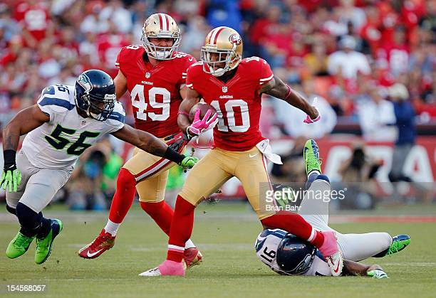 Wide receiver Kyle Williams of the San Francisco 49ers twists away from defensive end Chris Clemons as linebacker Leroy Hill of the Seattle Seahawks...