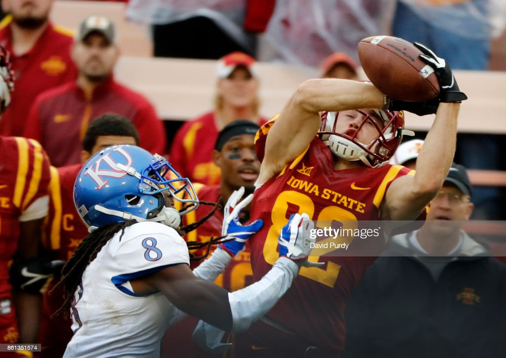 Wide receiver Landen Akers #82 of the Iowa State Cyclones pulls in a pass as cornerback Shakial Taylor #8 of the Kansas Jayhawks blocks in the second half of play at Jack Trice Stadium on October 14, 2017 in Ames, Iowa. The Iowa State Cyclones won 45-0 over the Kansas Jayhawks.