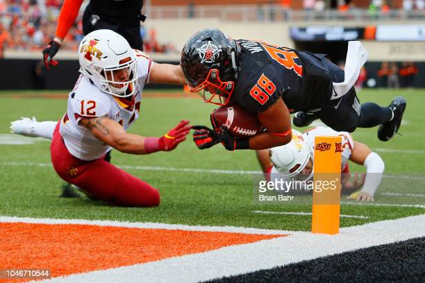Wide receiver Landon Wolf of the Oklahoma State Cowboys dives into the end zone for a touchdown against defensive back Greg Eisworth and defensive...