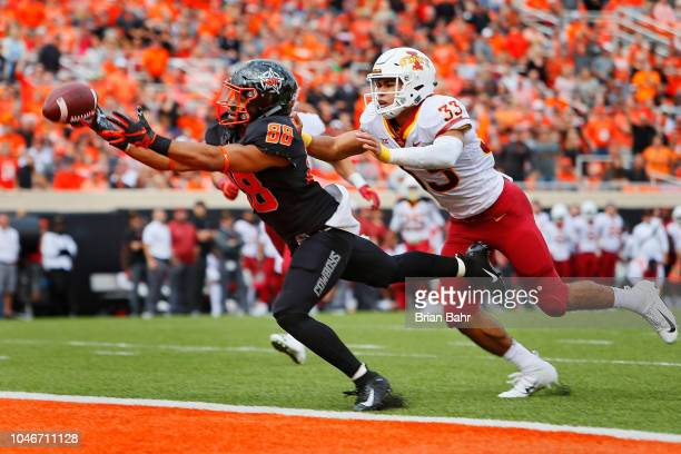 Wide receiver Landon Wolf of the Oklahoma State Cowboys stretches only to have the ball go through his fingertips against defensive back Braxton...