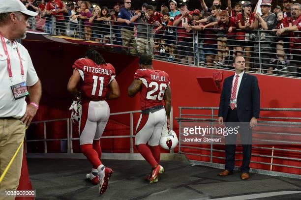 Wide receiver Larry Fitzgerald and defensive back Jamar Taylor of the Arizona Cardinals walk off the field after the NFL game against the Chicago...