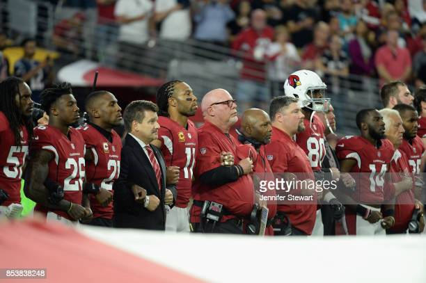 Wide receiver Larry Fitzgerald and head coach Bruce Arians of the Arizona Cardinals link arms during the National Anthem before the start of the NFL...