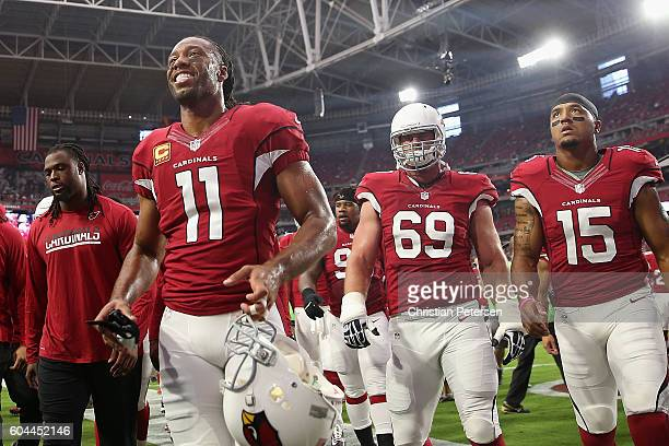 Wide receiver Larry Fitzgerald guard Evan Mathis and wide receiver Michael Floyd of the Arizona Cardinals walk off the field before the NFL game...