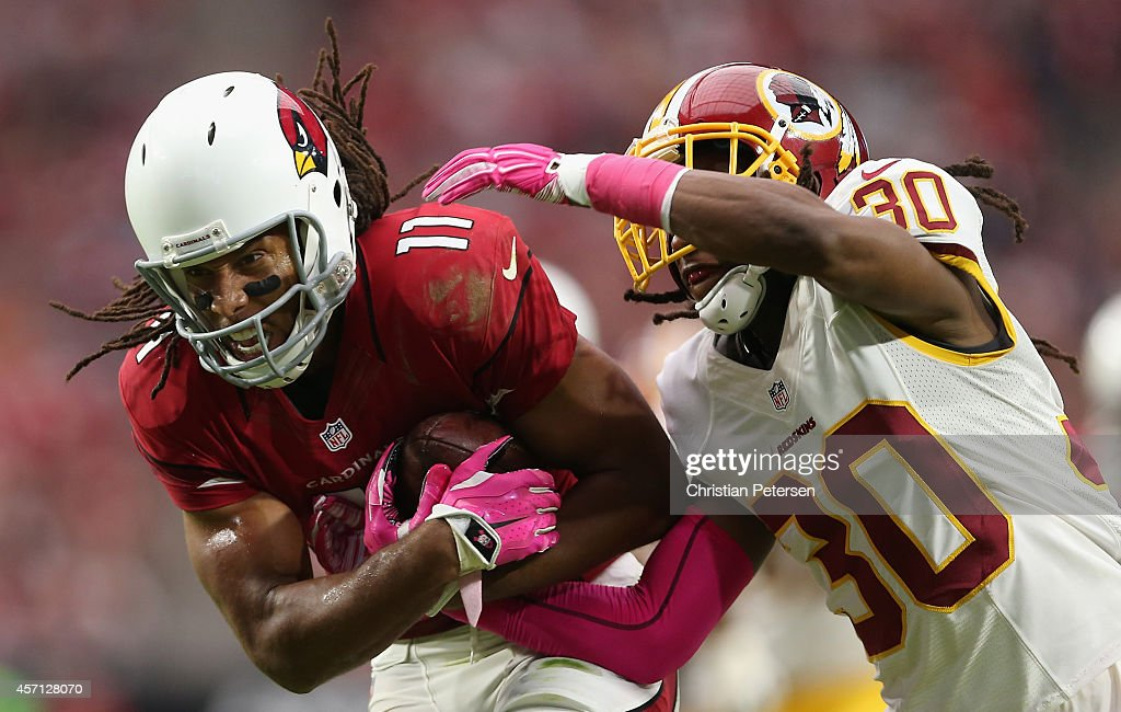 Wide receiver Larry Fitzgerald #11 of the Arizona Cardinals carries the football past free safety E.J. Biggers #30 of the Washington Redskins en route to scoring a 24 yard touchdown reception during the second quarter of the NFL game at the University of Phoenix Stadium on October 12, 2014 in Glendale, Arizona.