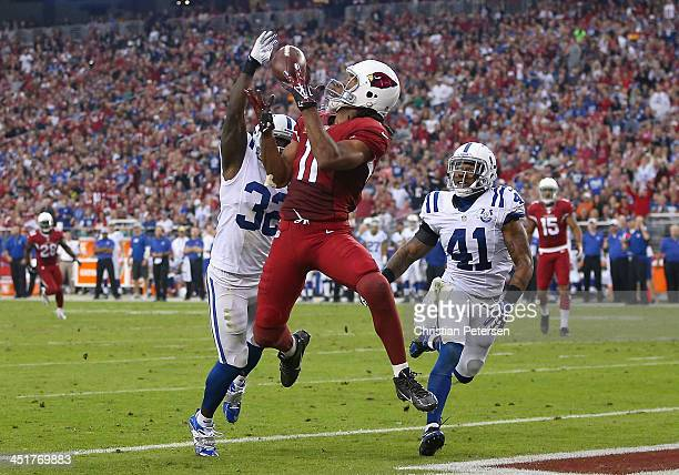 Wide receiver Larry Fitzgerald of the Arizona Cardinals catches a touchdown reception past cornerback Cassius Vaughn strong safety Antoine Bethea of...