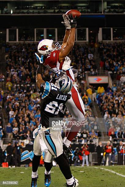 Wide receiver Larry Fitzgerald of the Arizona Cardinals catches a pass against the Ken Lucas and Charles Godfrey of the Carolina Panthers during the...