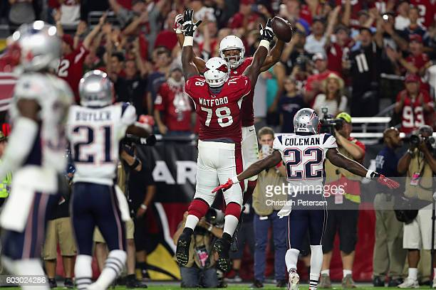 Wide receiver Larry Fitzgerald of the Arizona Cardinals celebrates his 100th career touchdown with offensive tackle Earl Watford during the fourth...