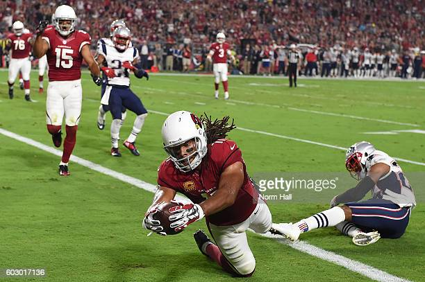 Wide receiver Larry Fitzgerald of the Arizona Cardinals dives in front of cornerback Logan Ryan of the New England Patriots to score a touchdown in...