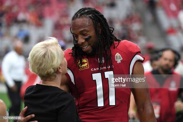 Wide receiver Larry Fitzgerald of the Arizona Cardinals hugs Cindy McCain the wife of late US Senator John McCain before the start of the game...