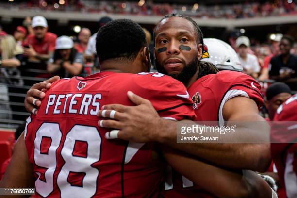 Wide receiver Larry Fitzgerald of the Arizona Cardinals hugs defensive tackle Corey Peters during the NFL game against the Carolina Panthers at State...