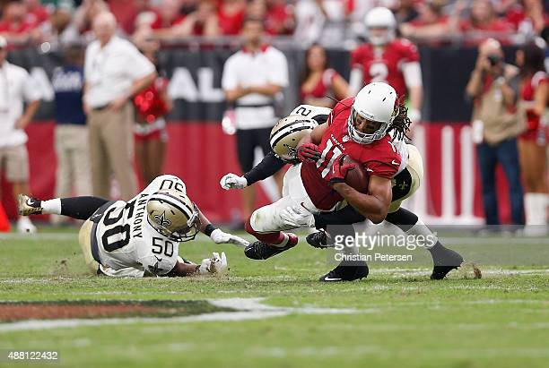 Wide receiver Larry Fitzgerald of the Arizona Cardinals is hit by inside linebacker Stephone Anthony of the New Orleans Saints and cornerback Damian...