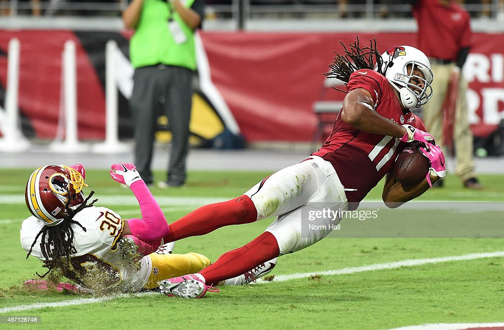 Wide receiver Larry Fitzgerald #11 of the Arizona Cardinals is hit in the end zone by cornerback E.J. Biggers #30 of the Washington Redskins during the second half against of the NFL game at University of Phoenix Stadium on October 12, 2014 in Glendale, Arizona.