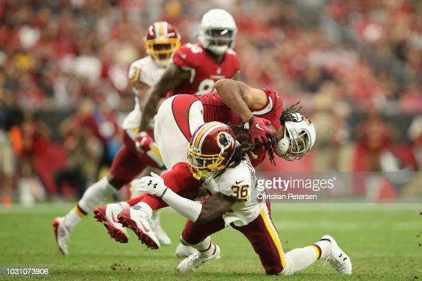 Wide receiver Larry Fitzgerald of the Arizona Cardinals is tackled by defensive back DJ Swearinger of the Washington Redskins after a reception...