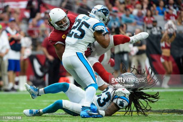 Wide receiver Larry Fitzgerald of the Arizona Cardinals is tackled by strong safety Eric Reid and cornerback Javien Elliott of the Carolina Panthers...