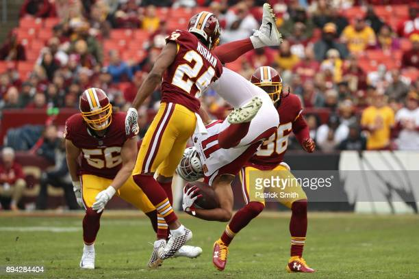 Wide receiver Larry Fitzgerald of the Arizona Cardinals is tackled by cornerback Josh Norman of the Washington Redskins during the first quarter at...