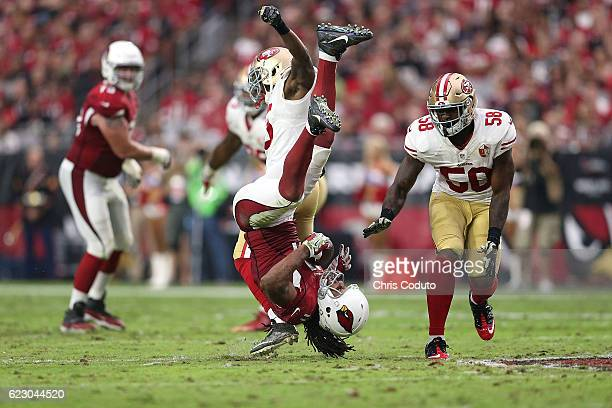 Wide receiver Larry Fitzgerald of the Arizona Cardinals is upended by cornerback Jimmie Ward of the San Francisco 49ers and outside linebacker Eli...